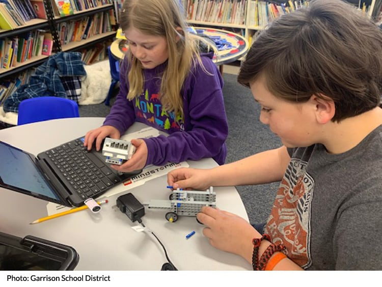 Students in a classroom with a robot and laptop